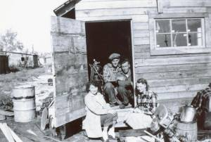 Sylvia sitting in the doorway of the small mechanic's shop, with Elmer and Kay Briem, and a young Dodi back from the war beside Mom.